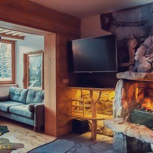 Ciepłe kakao w zimowy mroźny dzień przy trzasku tlącego się drewna – kominek w domu domowe ognisko ciepło ogień kominek